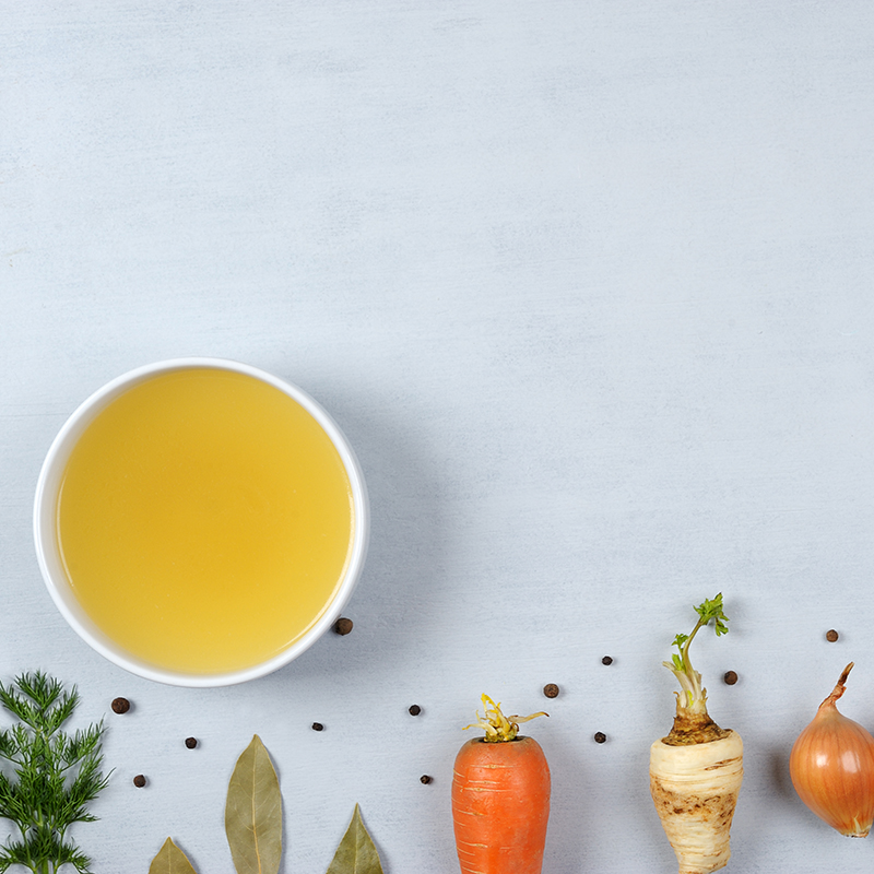 Homemade broth in white bowl on the grey background.